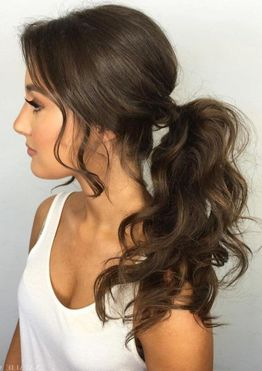 Wavy hair low ponytail hairstyles for women with long bangs